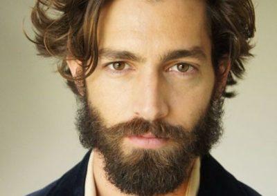 taglio-uomo-medio-lungo-tendenza-ciuffo-lato-mosso-barba-baffi-folti-giacca-camicia-aperta